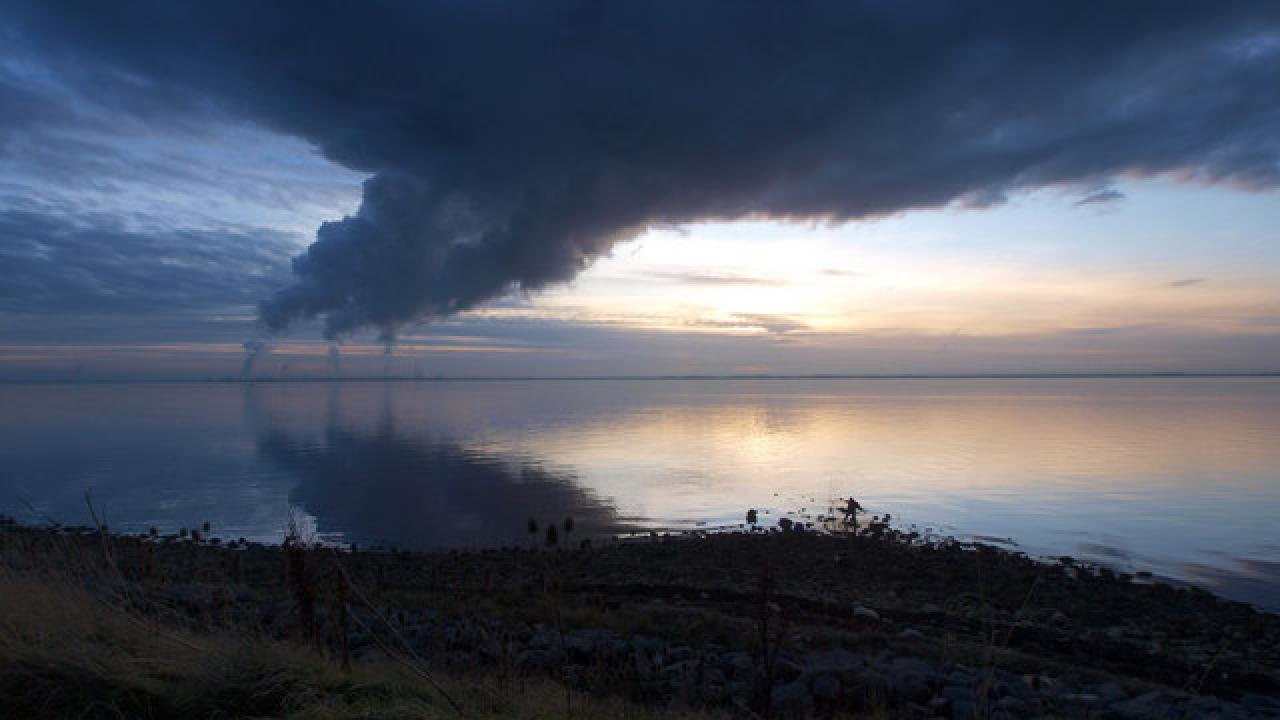 Image: a photo of a body of water with industrial stacks emitting large plumes of pollution.