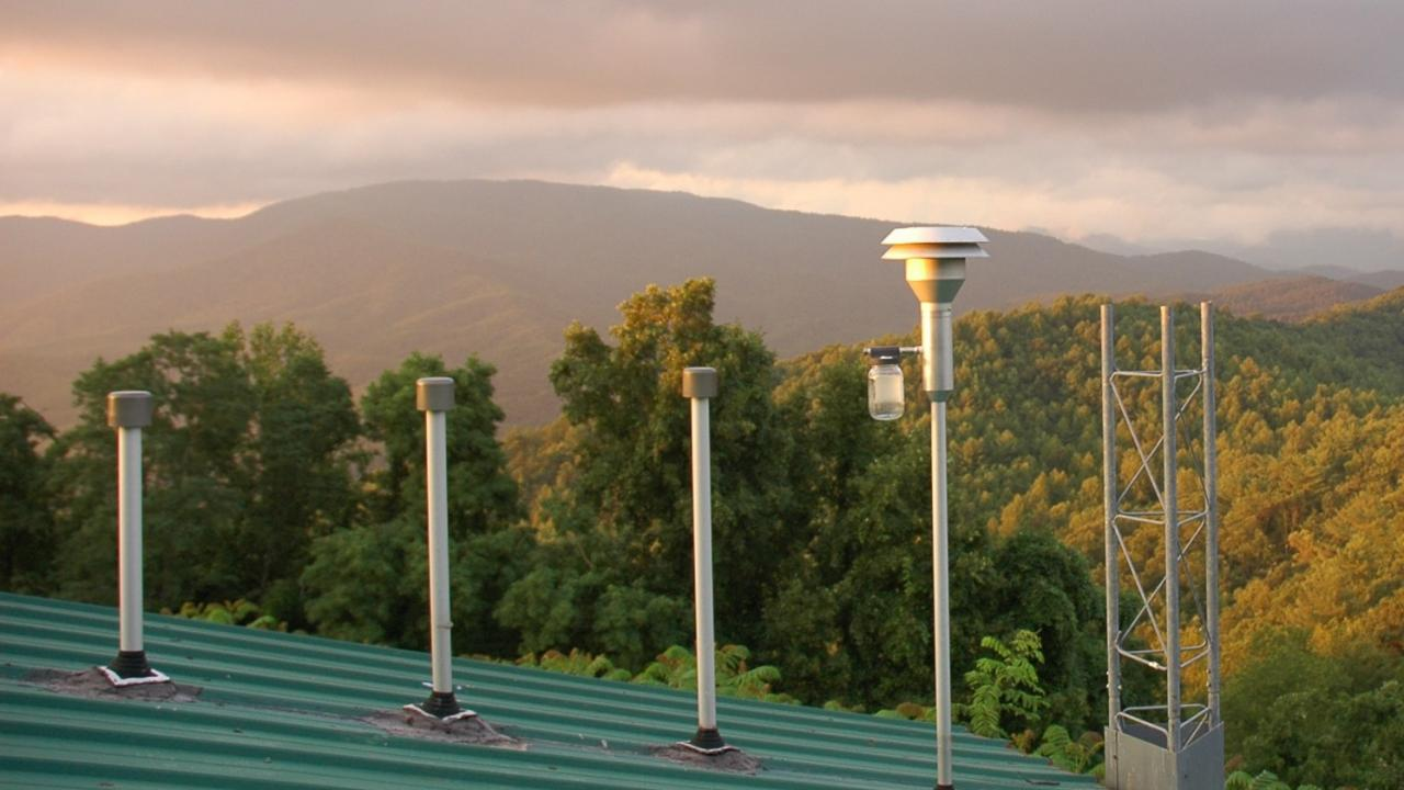 Image: inlet stacks of monitoring station surrounded by forested mountains.