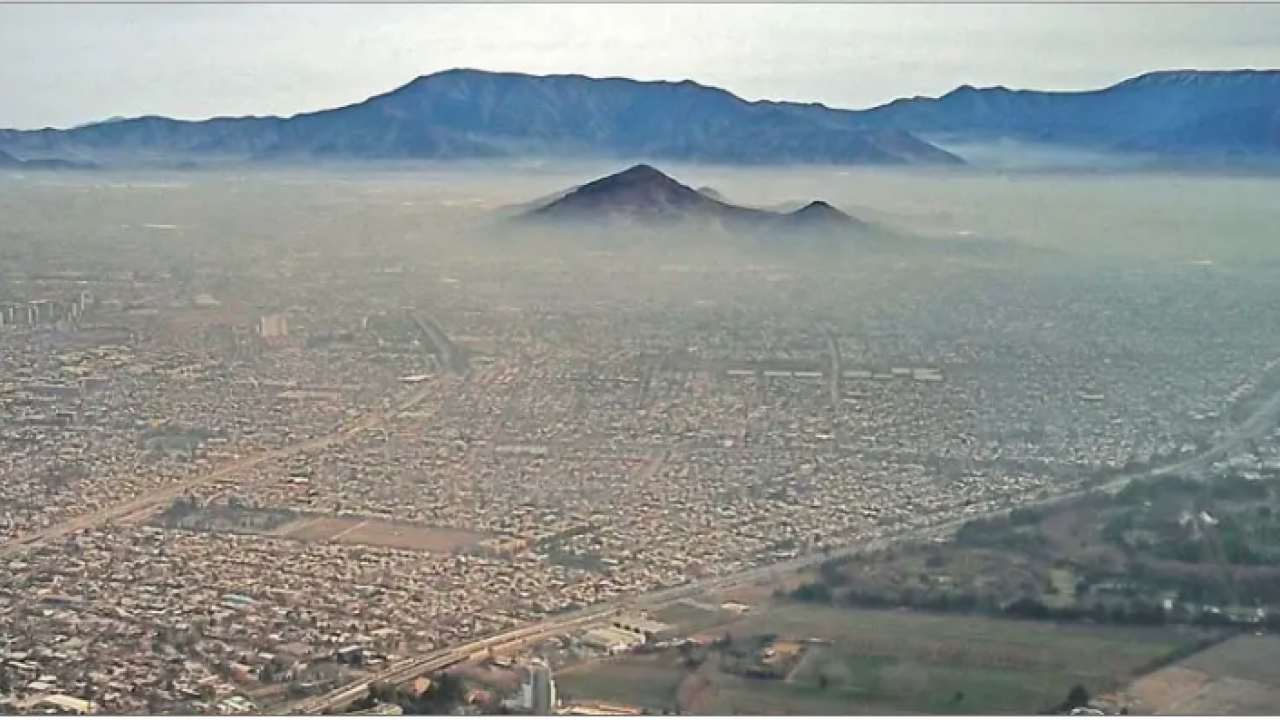 Image: a metropolitan area blanketed by pollution.