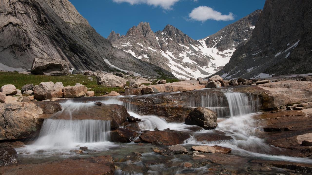 Image: a photograph of small, rushing falls of water over rocks at Titcomb Basin Cascade.