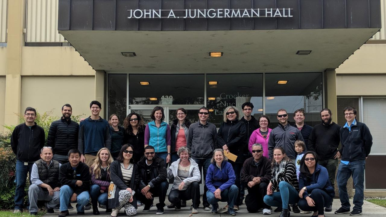 Image: members of the Air Quality Research Center stand in front of a campus building.