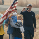 Image: people outside wear face masks and wave an American flag.