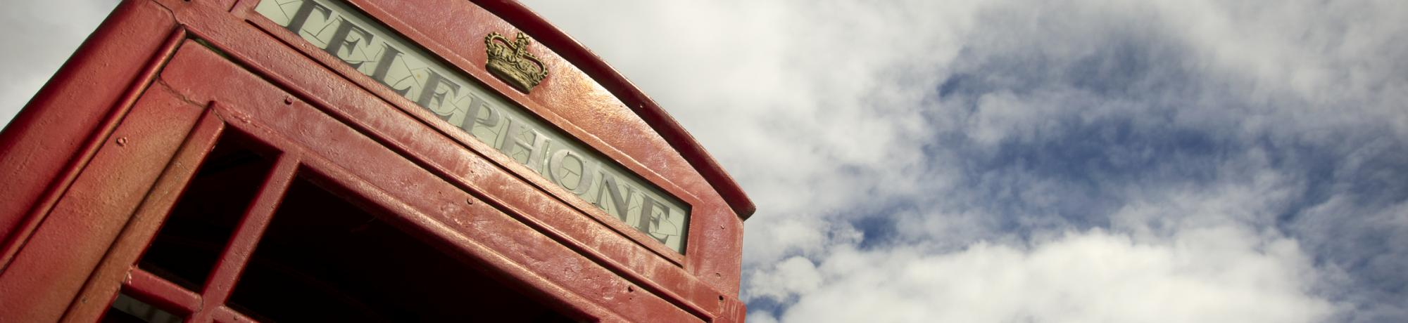 Image: vintage red phone booth and cloudy blue sky overhead.