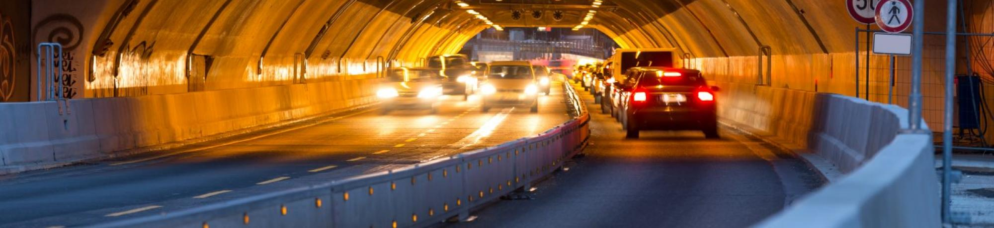 Image: a vehicular tunnel with cars driving through.