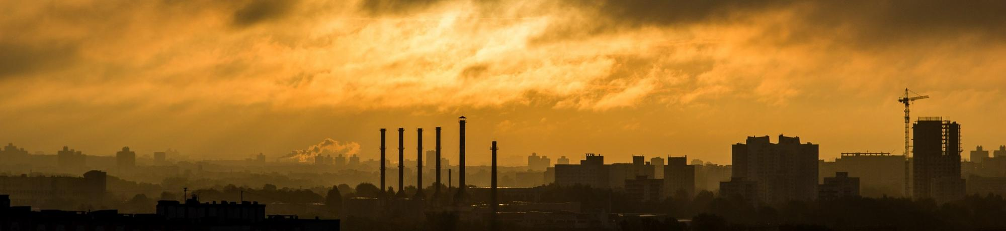 Image: a industrial emissions envelope a metropolitan area at dusk. Image by Free-Image of Pixabay. End ID.